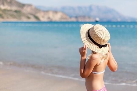 Little girl is at sea beach in summer vacation. Cute kid in straw hat is happy tourist in resort outdoors. Holiday, travel and summertime concept. Child is looking at view of ocean, island, mountains. 写真素材 - 135180862