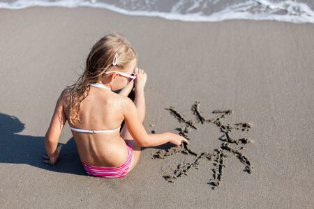 Kid is drawing sun in sand at beach. Concept of children picture, sand painting at summer vacation, holiday and travel. Little girl is sitting in waves outdoors. Child is enjoying summertime. 写真素材 - 135180858
