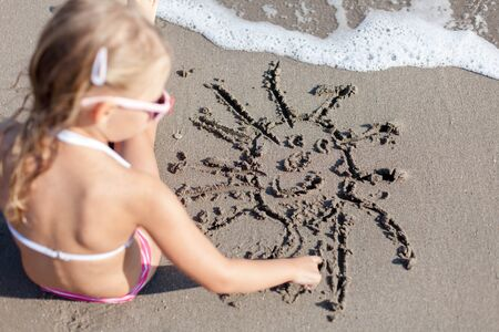 Kid is drawing smiling sun on sand at beach. Concept of children picture, sand painting at summer vacation, holiday and travel. Little girl is sitting in waves outdoors. Child is enjoying summertime.