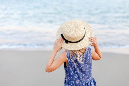 Little girl is at sea beach in summer vacation. Cute kid in straw hat is tourist in resort outdoors. Concept of children holiday, travel, tenderness, femininity. Child is looking at view of ocean.