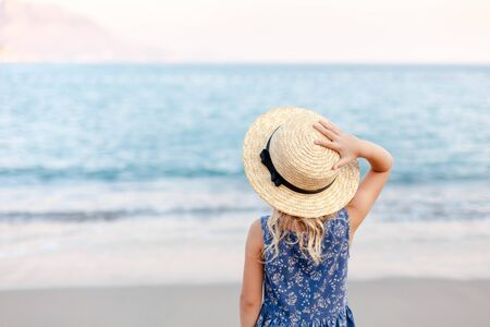 Little lady girl is at sea beach in summer vacation. Cute kid in straw hat is tourist in resort outdoors. Concept of children holiday, travel, tenderness, femininity. Child is looking at view of ocean