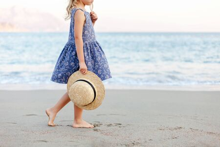 Little lady girl at beach in summer vacation. Cute kid in blue dress holds straw hat. Concept of children holiday, travel, tenderness, femininity. Child is walking at seaside outdoor.