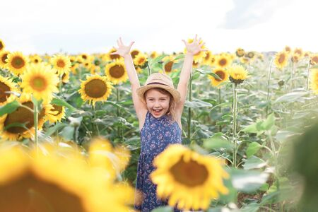 Funny kid in sunflowers in summer vacation. Child girl in straw hat and blue dress is smiling, laughing. Concept of holiday, happiness and enjoying life. Lifestyle, authentic moments, emotions.