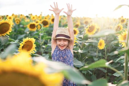 Funny kid in sunflowers field on summer holiday. Child girl in straw hat and blue dress is smiling, laughing. Concept of happiness, vacation and enjoying life. Lifestyle, authentic moments, emotions. 写真素材