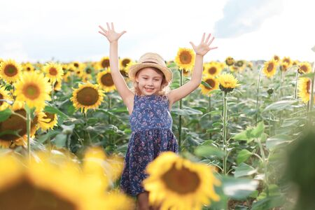 Happy kid in sunflowers field in summer vacation. Child girl in straw hat and blue dress is jumping, smiling. Concept of holiday, happiness and enjoying life. Lifestyle, authentic moments, emotions. 写真素材