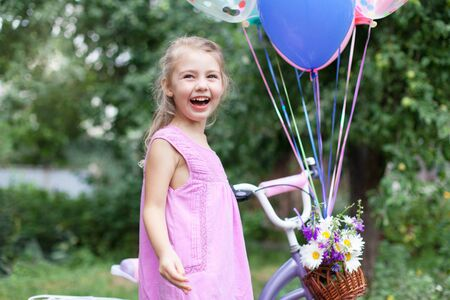 Little girl is surprised of Happy Birthday gift. Kid gets bicycle with balloons, basket with bouquet of summer flowers. Child is smiling, having fun, laughing. Lifestyle moment, real candid emotions. 写真素材