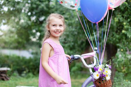 Little girl gets Birthday gift. Kid holds bicycle with balloons and wicker basket with bouquet of summer flowers. Child is smiling. Lifestyle moment. Celebration of children party outside in garden.