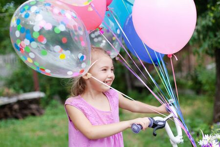 Little girl gets bicycle with balloons. Kid with gift or present. Child is smiling, having fun. Celebration of Happy Birthday party outside in summer backyard. Lifestyle moment, candid real emotions.