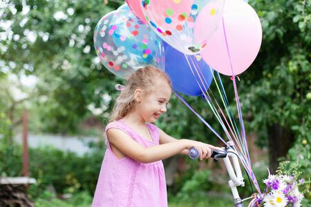 Little girl gets bicycle with balloons. Kid with gift or present. Child is smiling, having fun. Celebration of Happy Birthday party outside in summer garden. Lifestyle moment, candid real emotions. 写真素材