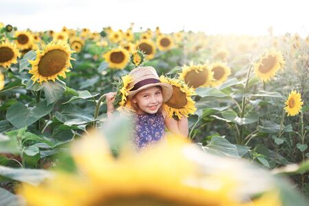 Happy child girl in sunflowers field on summer holiday. Kid in straw hat and blue dress is smiling, laughing. Concept of happiness, vacation and enjoying life. Lifestyle, authentic moments, emotions. 写真素材 - 135181623