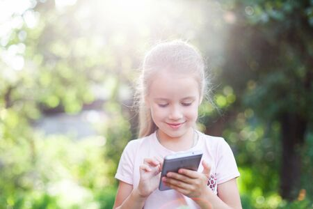 Kid is using mobile phone. Child is smiling and looking at screen of devices. Little girl is playing in children digital games in green park or garden outside. 写真素材