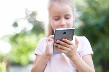 Kid is using mobile phone. Child is smiling and looking at screen of devices. Little girl is playing in children digital games at green background.