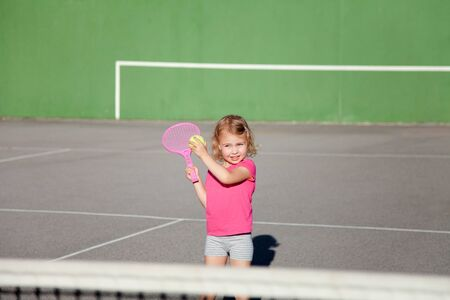 Kid is playing tennis on court. Cute child is having fun playing sports activities outdoors. Little girl has practice in summer game.