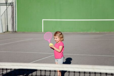 Kid is playing tennis on court. Cute child is having fun in sports activities outdoors. Little girl has practice game in summer.
