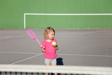 Kid is playing tennis on court. Cute child has workout. Sports activities outdoors in summer. Little girl is having fun. 写真素材