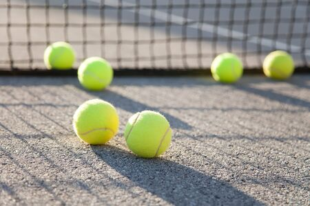 Six tennis balls by net on tennis court. Concept of workout, summer sports activities and playing outdoors.