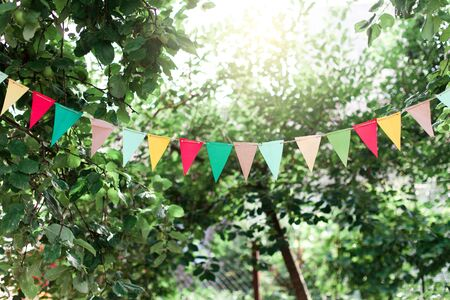 Garland of colorful flags at sunset in summer garden and backyard. Concept of celebration Happy Birthday party. Paper festive decoration outdoor.