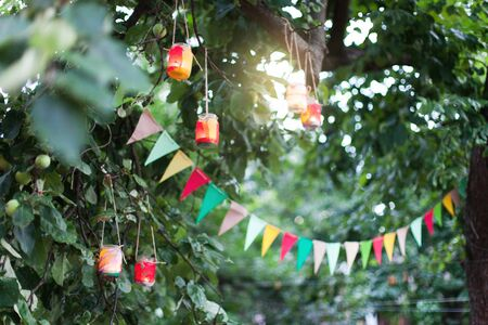 Garland of colorful flags and homemade flashlights at sunset in summer garden. Concept of celebration Happy Birthday party. Paper festive decoration outdoor.