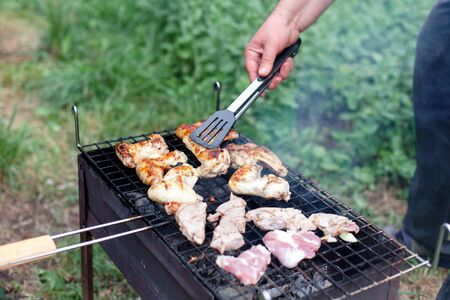 Man is cooking barbecue. Picnic with grilled meat. Bbq party in summer backyard.