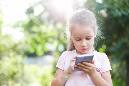 Child is using mobile phone. Kid is looking at screen of devices. Little girl is playing on digital gadget in green park or garden outside. Concept of internet and games addiction. 写真素材