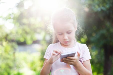 Kid is using mobile phone. Child is looking at screen of devices. Little girl is playing in children digital games in green park or garden outside.