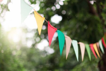 Garland of colorful flags at sunset in summer garden. Concept of celebration Happy Birthday party. Paper festive decoration outdoor. Green background. 写真素材