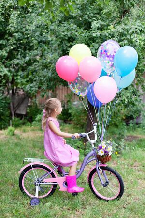 Little girl is riding on pink bicycle with balloons and wicker basket with bouquet of summer flowers. Kid gets gift. Celebration of Happy Birthday children party outside in summer garden in backyard.