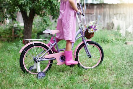 Little girl is riding on lilac bicycle with wicker basket with bouquet of summer flowers. Kid is wearing in pink dress and rubber boots. Child is playing in backyard garden. 写真素材