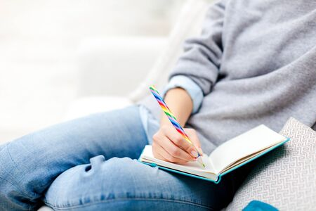 Female hand with rainbow pencil is writing goals in notebook. Freelancer is working in cozy place. Girl is planning and dreaming. Young woman is sitting on comfortable sofa. Close up.