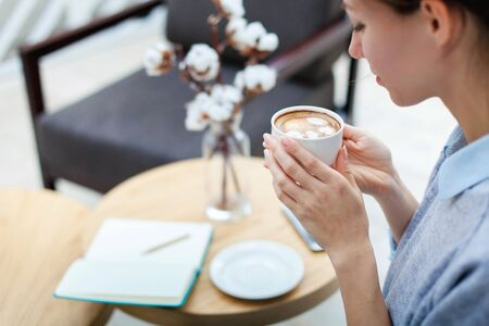 Young woman is enjoying and drinking coffee. Freelancer is working and writing in notebook in cozy cafe. Girl is planning and dreaming. Wellbeing in workplace.