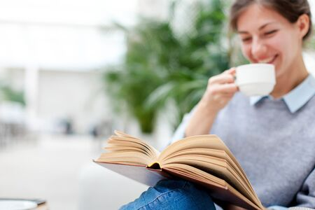 Young woman is drinking coffee and reading book. Girl is smiling, enjoying relaxation and sitting on sofa in cozy modern cafe indoors. 写真素材