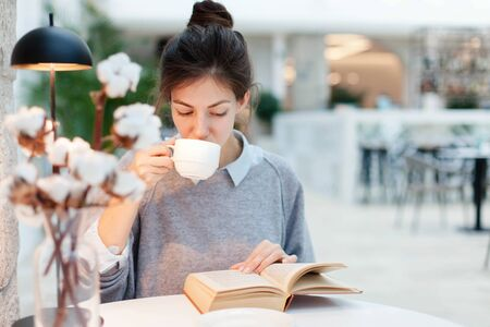 Young woman is drinking coffee and reading book under warm table lamp light. Girl is sitting in cozy modern cafe indoors. 写真素材