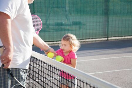 Kid is playing tennis on court. Cute child girl has workout with teacher or trainer. Sports activities outdoors in summer. 写真素材