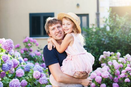 Happy father with daughter are hugging in bushes of hydrangea flowers outdoors. Sunset garden by house. Little kid girl is daddys princess. Concept of family love, tenderness, Fathers Day.