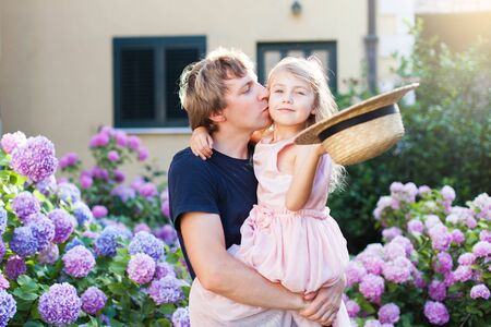 Father is kissing daughter in bushes of hydrangea flowers outdoors. Sunset garden by house. Little kid girl is daddys princess. Concept of family love, happiness, tenderness.