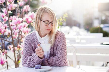 Young woman is drinking coffee in cafe on spring city streets. Blooming bushes of flowers are pink and purple. Attractive girl is enjoying of magnolia garden at sunset outside.