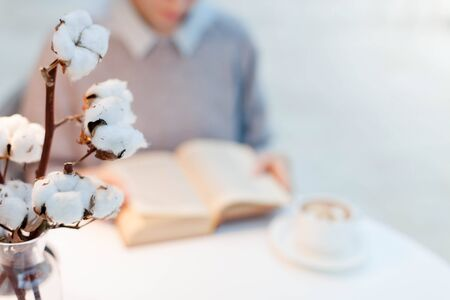 Young woman is reading opened book at table with cotton flowers. Girl is drinking coffee in cozy modern cafe indoors. Blurred background. Close up. 写真素材
