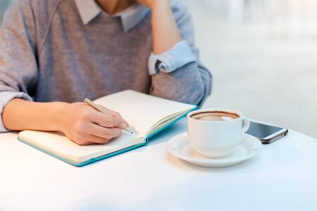 Young woman is writing in notebook in cozy cafe with cup of coffee. Freelancer is working in comfortable coworking modern place. Girl is planning and dreaming. Wellbeing in workplace.