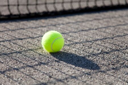 One tennis ball by net on tennis court. Concept of workout, summer sports activities and playing outdoors. 写真素材
