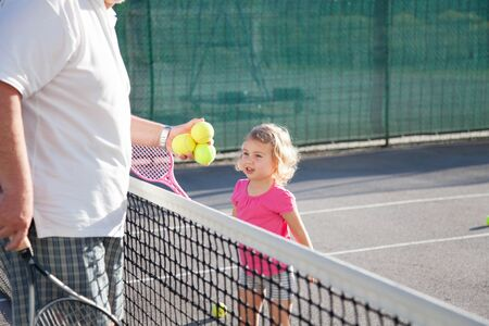 Kid is playing tennis on court. Cute child has workout with teacher or trainer. Sports activities outdoors in summer. Little girl is having fun. 写真素材