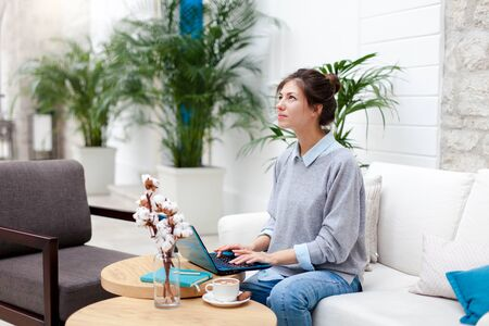 Freelancer is working in comfortable cafe. Happy girl with laptop in coworking modern office. Attractive businesswoman is dreaming, thinking, enjoying coffee and quiet space. Wellbeing in workplace.