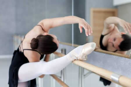 Ballerina is doing exercises in ballet classical school. Girl is stretching with leg in pointe shoes on barre. Woman has dance workout. 写真素材