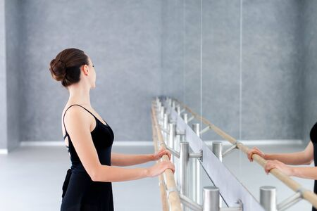 Ballerina is doing exercises in ballet class room. Dancer is putting hands on barre in front of mirror. Girl has dance workout.