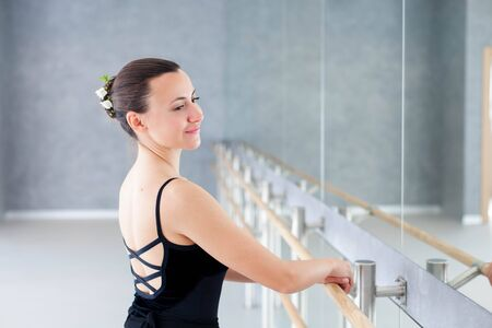 Ballerina is doing exercises in ballet classical school. Girl is smiling and putting hands on barre. Woman has dance workout. 写真素材