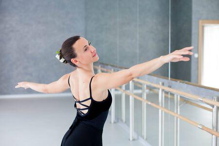 Ballerina is dancing in ballet classical school. Dancer is doing exercises near barre in front of mirror. Girl has dance practice or workout.