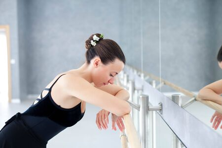 Tired ballerina has break in dance workout in ballet class room. Girl is putting hands on barre in front of mirror.