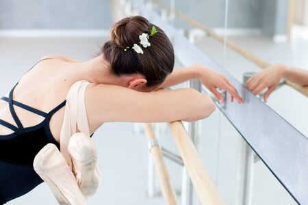 Tired ballerina with pointe shoes has rest in dance practice in ballet classical school. Girl is putting hands and head with spring flowers on barre. 写真素材