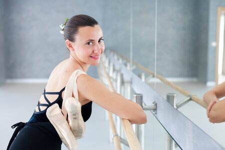 Ballerina with pointe shoes is smiling and finishing dance workout in ballet class room. Girl is putting hands on barre in front of mirror.