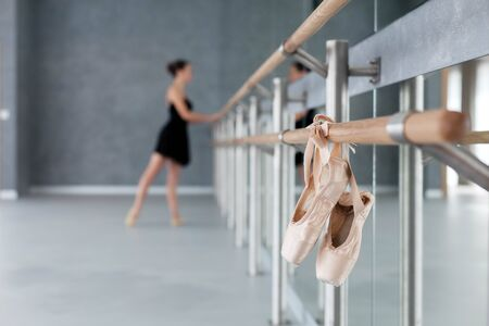 Pointe shoes hang on ballet barre. Blurred background with ballerina doing exercises. Girl has dance workout in front of mirror in ballet classic school. 写真素材