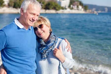 Senior couple is laughing, smiling at sea beach outdoor. Happy man and woman are hugging, traveling, enjoying retirement. Concept of wellbeing, love, happiness. Lifestyle, authentic moments, emotions. 写真素材